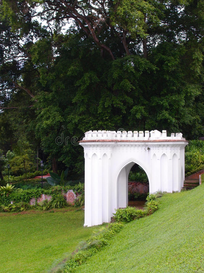 Antique British style folly in hillside garden. A photograph showing the beautiful classical antique style architecture of an English garden folly shelter, built royalty free stock photo
