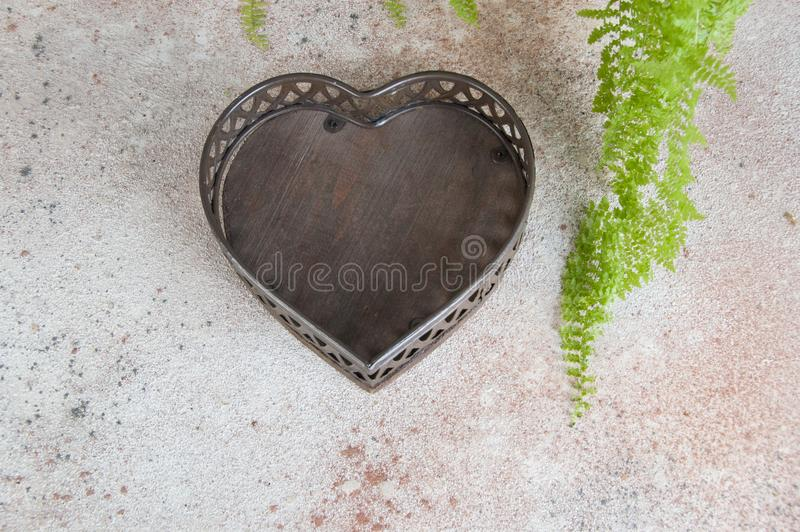 Antique brown basket on concrete background. Antique brown basket shape of the heart on concrete background. Copy space for text royalty free stock photos