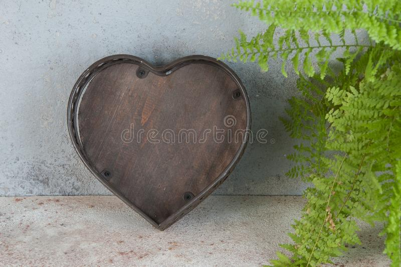 Antique brown basket on concrete background. Antique brown basket shape of the heart on concrete background. Copy space for text stock image