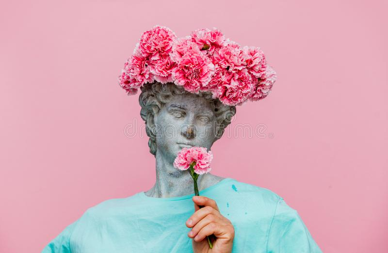 Antique bust of male with carnations bouquet in a hat. On pink background. Ready for summer vacation stock images
