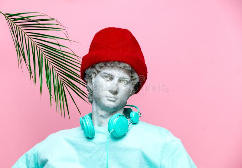 Antique bust of male in hat with headphones on pink background. stock images