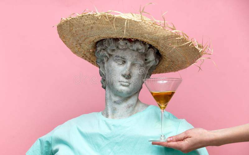 Antique bust of male in hat with martini glass. On pink background. Ready for summer vacation stock photo