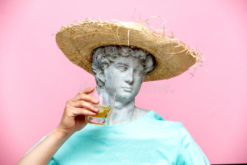 Antique bust of male in hat with whiskey glass. On pink background. Ready for summer vacation royalty free stock photo