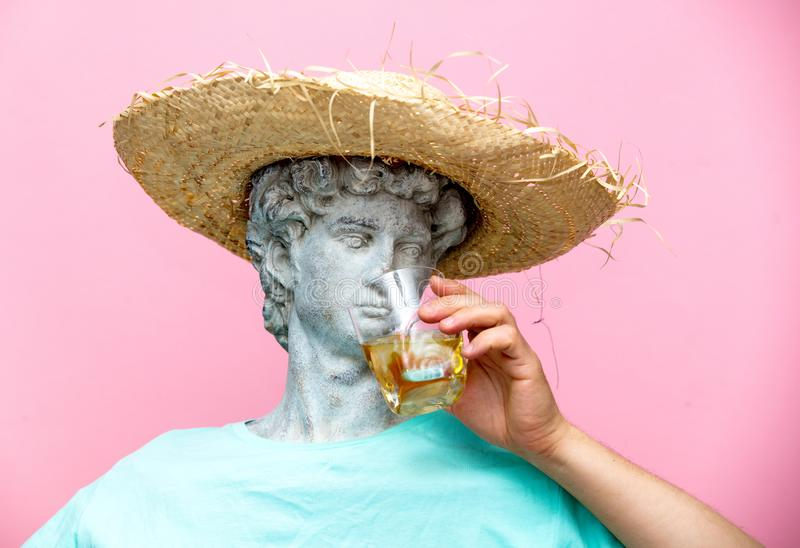 Antique bust of male in hat with whiskey glass. On pink background. Ready for summer vacation stock photos