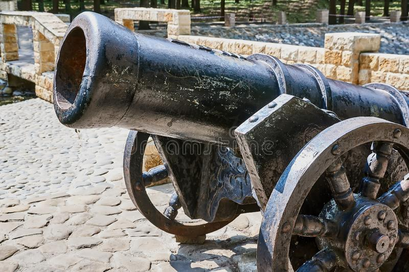 Antique cannon. Stands on the pier with paved paving stones against the background of the forest. Old cannon large. Ancient black cannon royalty free stock photos