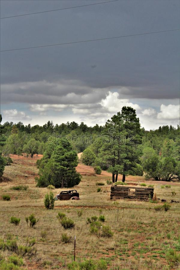 Antique Car and partial log cabin in Linden, Navajo County, Arizona, United States. Antique Car and partial abandoned log cabin in a field surrounded by trees stock image