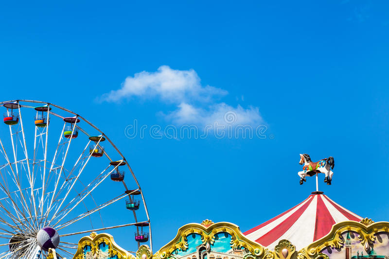 Antique carousel horses tent in amusement park with colourful ferris wheel stock photo
