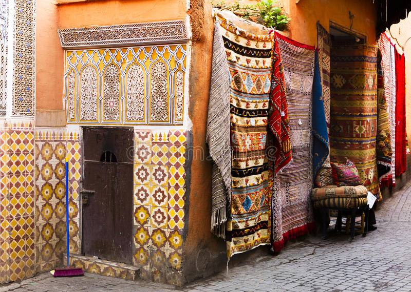 Antique carpets and tiled wall in Marrakesh royalty free stock images