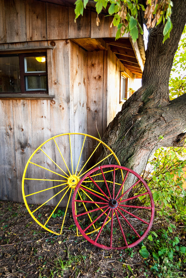 Antique carriage wheels by the farm house wall. royalty free stock photos