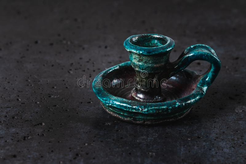 Antique ceramic candlestick of turquoise color on gray cement background, ancient object designed for candles representing royalty free stock images