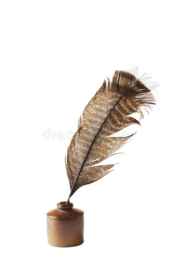 Antique ceramic ink well and feather quill pen. Quill feather pen stands in antique ceramic ink well. Brown glaze, striped feather in diagonal position. Vertical royalty free stock image