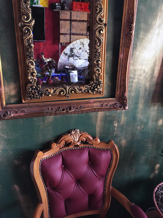 Antique Chair and Mirror. Interior of an antique shop, with an elaborate gilt framed mirror and a chair upholstered in royal purple satin fabric royalty free stock image