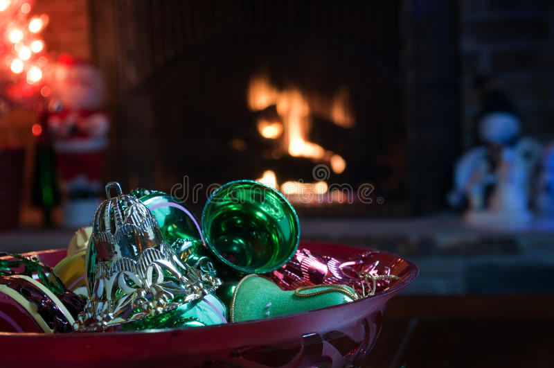 Antique Christmas ornaments. Including silver, green, and red bells, in a red bowl. The bowl is sitting in front of a fireplace. In the background are stock photos