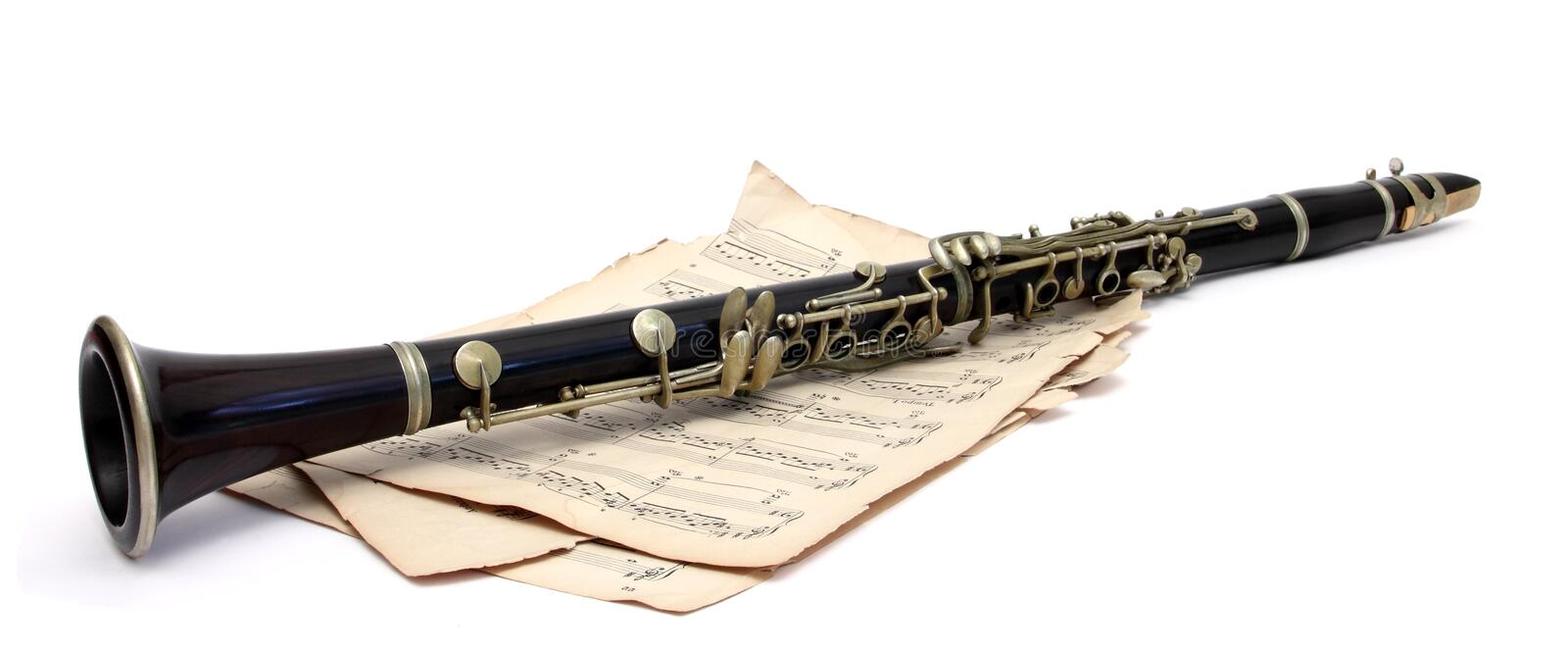 Antique clarinet. An old clarinet on music sheets over white stock image
