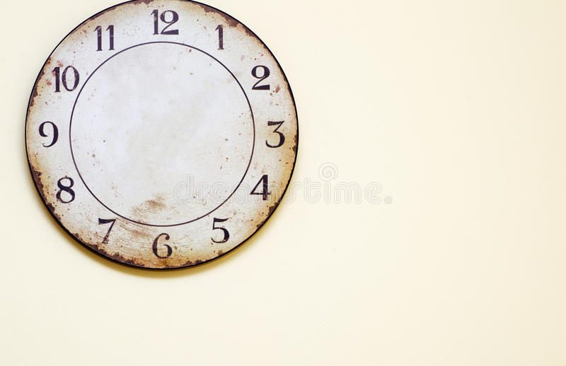 Antique clock hanging on the wall. Old round watch on a yellow background royalty free stock photos
