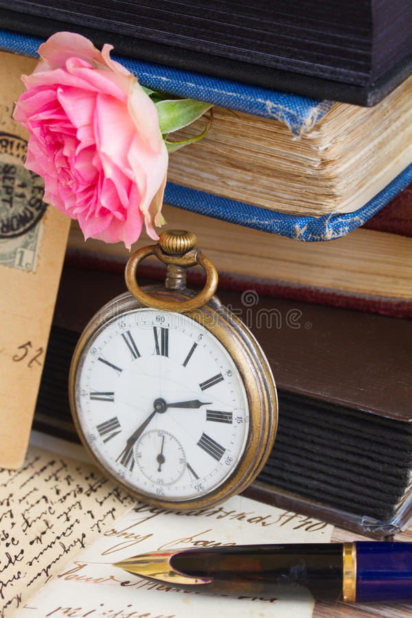 Antique clock on old books and letters background royalty free stock photography