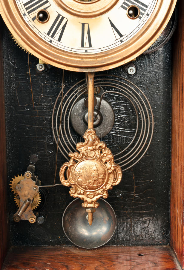 Antique clock works. Showing the pendulum, springs, chimes and part of the face stock photo