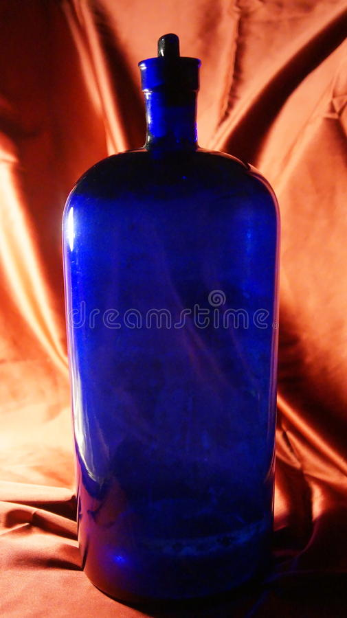 Antique cobalt blue apothecary bottle. Large Antique cobalt blue apothecary bottle with back-lighting. photographed against a gold satin background. Used as an royalty free stock image