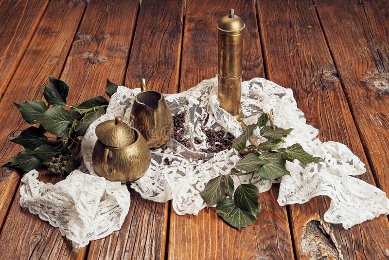 An antique coffee grinder made of brass, a brass milk jug and a brass sugar bowl, presented on an old, wooden table top with a royalty free stock photos