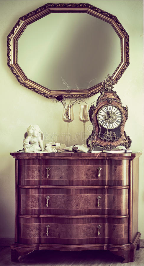 Antique commode with a mantel clock. Antique wooden commode with a baroque style ornate mantel clock and wooden framed wall mirror for a vintage style interior royalty free stock photography