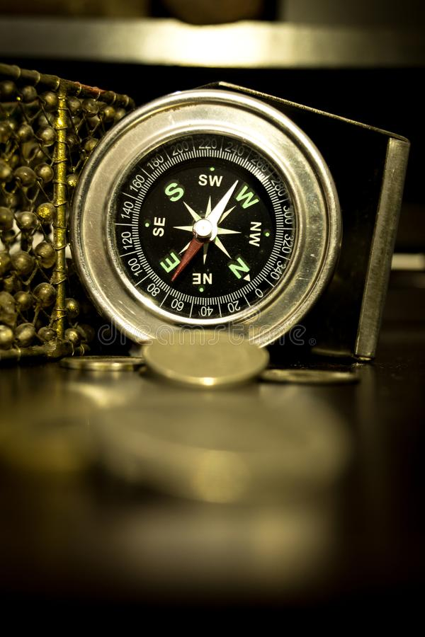 Antique compass and brass coins. stock images