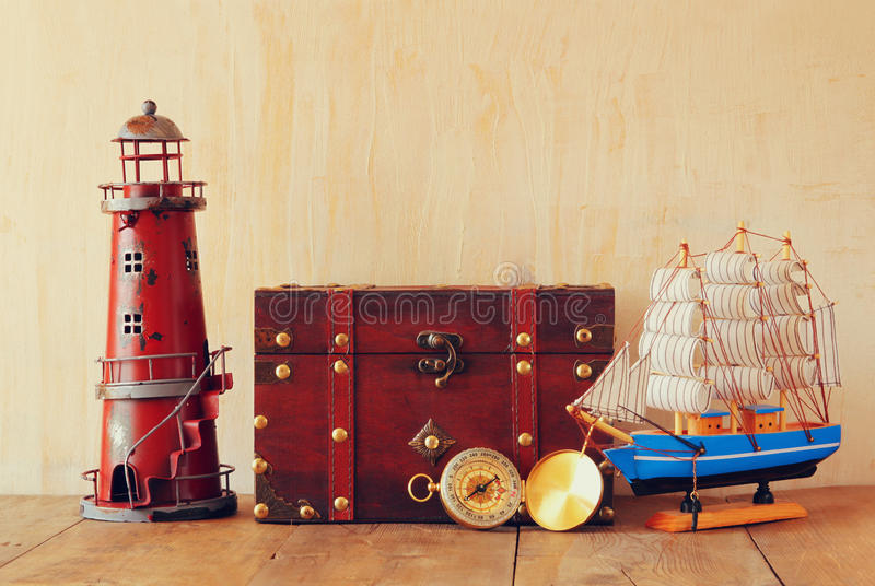 Antique compass, vintage lighthouse, wooden boat and old chest on wooden table royalty free stock photo