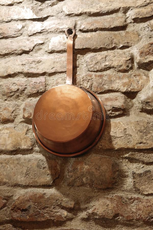 Antique copper cookware. On a brick wall stock photography
