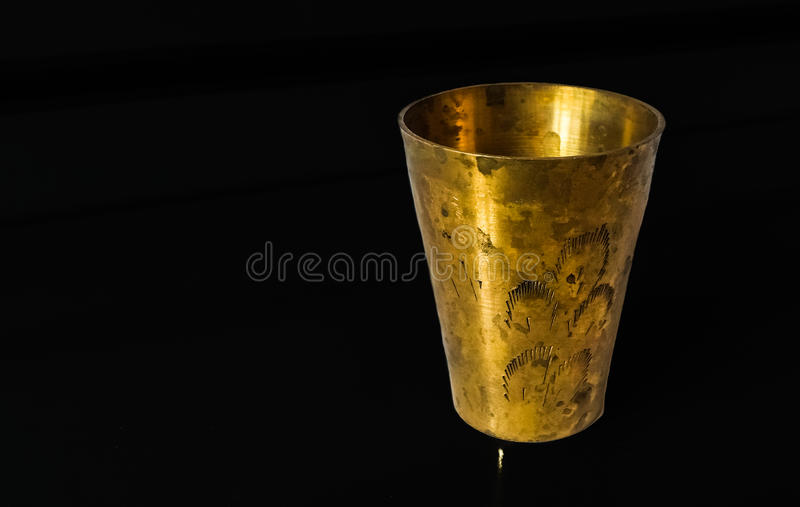 Antique copper cup. On a black background stock images