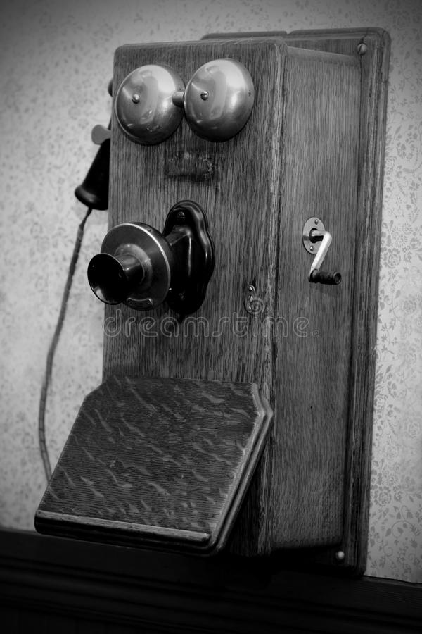 Antique crank phone (BW). An antique crank phone hanging on the wall. Shallow depth of field stock image