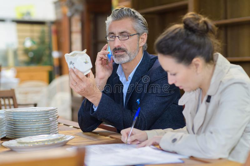 Antique dealer inspecting object assistant making notes beside him royalty free stock photos