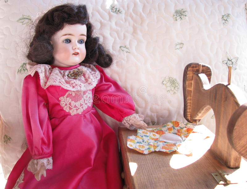 Antique Doll with her Sewing Machine. Antique doll with a toy sewing machine and a quilt piece stock photos