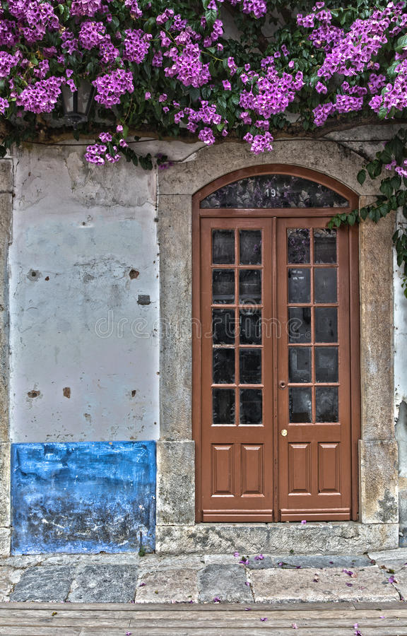Antique Door near Purple Flowers in the Medieval Portuguese City stock photo