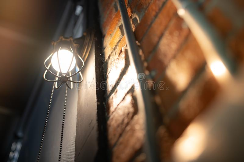 Antique electronic lamp, red wall lamp, high wall lamp, soft light.Red brick wall.Open chain, turn off the lights.hanging at the r royalty free stock photo