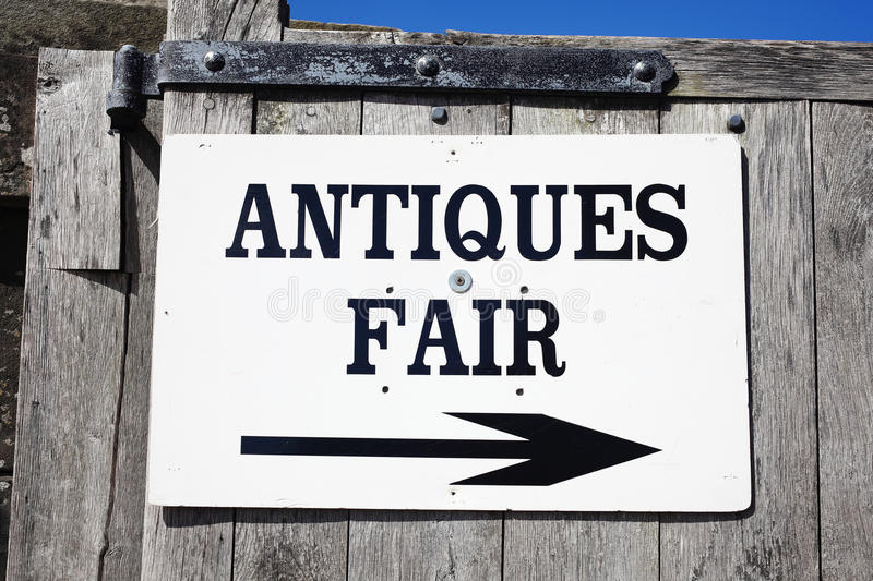 Antique fair sign. Antique sign directing buyers to an outdoor antiques retail fair stock photos