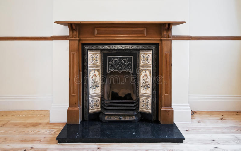 Antique fireplace. With carved wooden frame and hand painted ceramic tiles stock photo