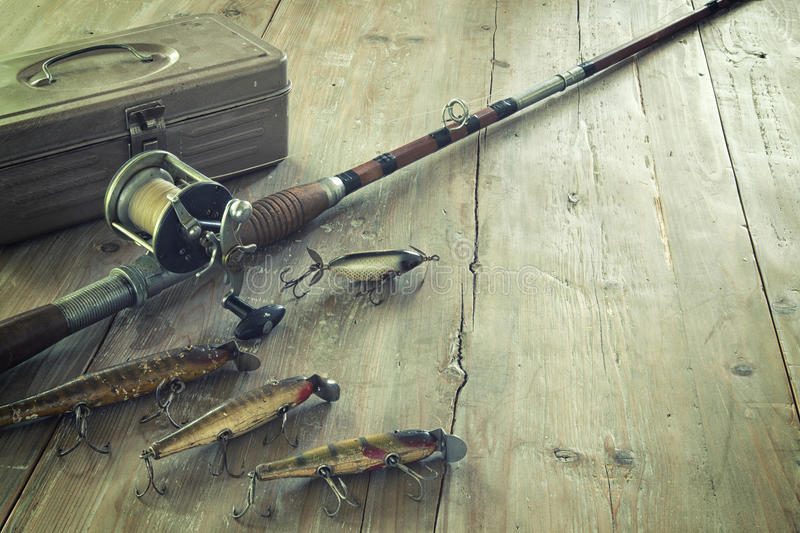 Antique Fishing Rod and Lures on a Grunge Wood Surface royalty free stock images