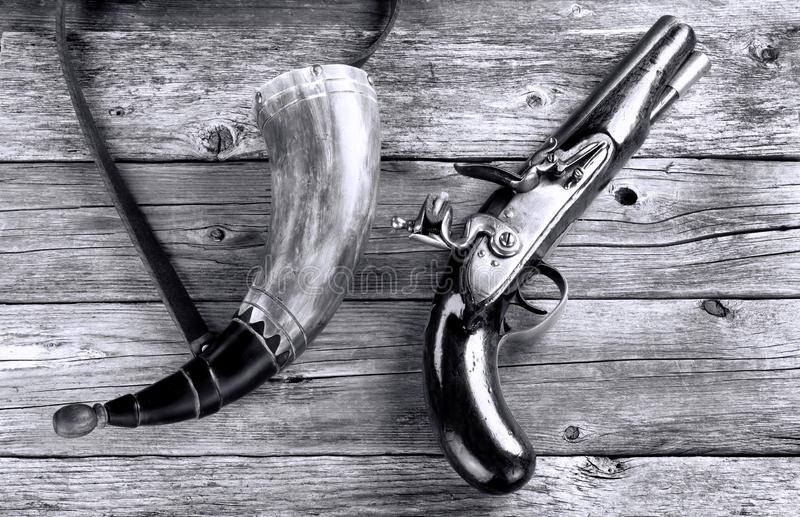 Antique Flintlock Pistol and Gunpowder Horn. Antique English flintlock pistol and gunpowder horn made around 1800 in black and white stock photo