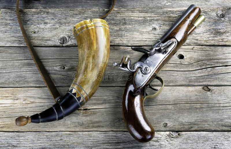 Antique Flintlock Pistol and Gunpowder Horn. Antique English flintlock pistol and gunpowder horn made around 1800 royalty free stock image