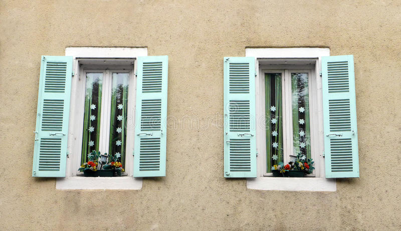 Antique French house window decor. A Photograph showing the antique design wood windows of an old rustic French house in the historic heritage city of Cahors stock photos