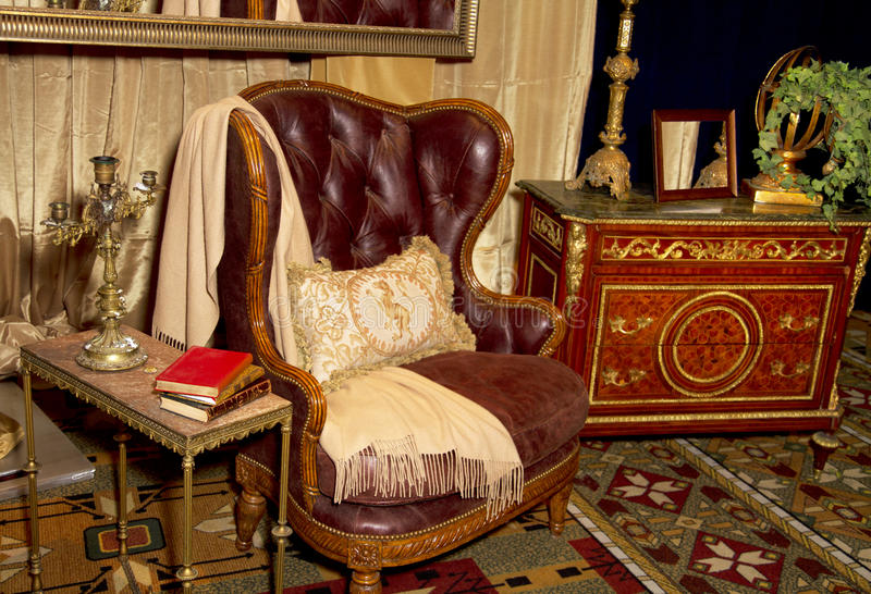 Antique Furniture Retail Store Setting. Antique furniture including dresser, table, leather chair, and brass lamps in a retail store design setting stock photos