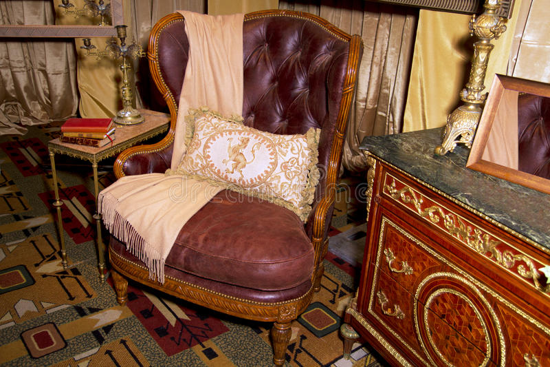 Antique Furniture Retail Store Setting. Antique furniture including dresser, table, leather chair, and brass lamps in a retail store design setting royalty free stock image