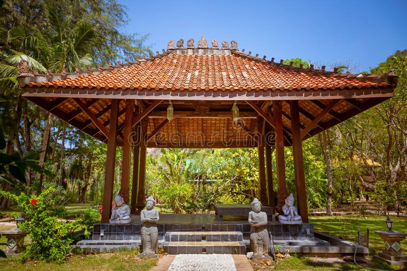 Antique gazebo pavilion with a roof asian style pagoda. In a summer tropical garden. A stone path along which the statues stand stock photos