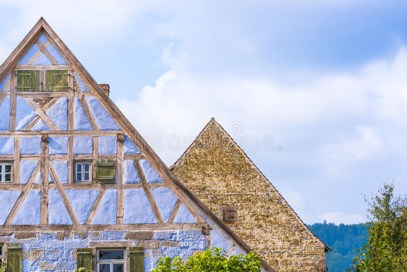 Antique German gable roofs and facades against sky. Architectural details from two medieval German houses , one with blue half timbered walls, small windows royalty free stock photography
