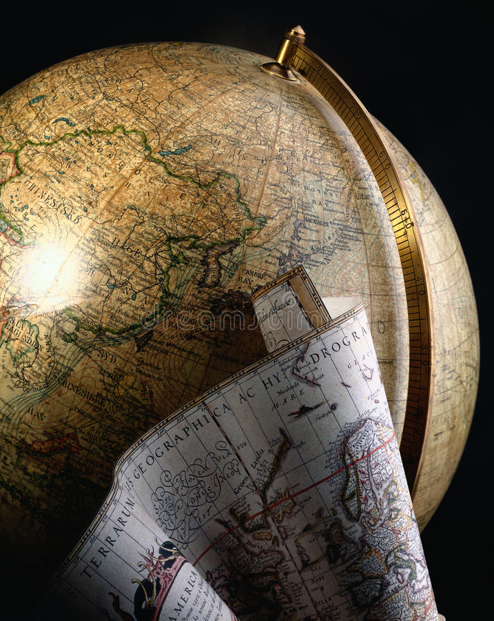 Antique globe and map of the world. An antique globe showing Asia with a map of the world in front royalty free stock photos