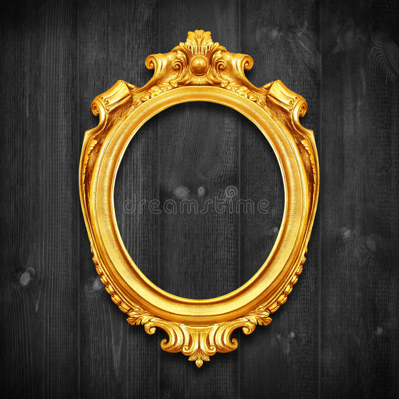 The Antique gold frame on wooden wall;. Empty Antique gold picture frame on wooden wall. stock image
