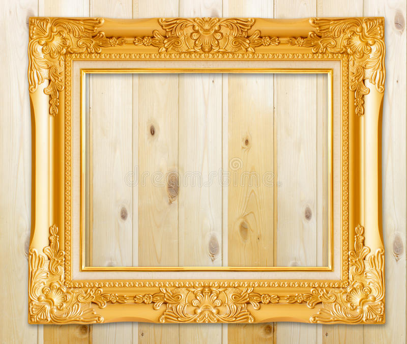 Antique gold frame on wooden wall;. Empty picture frame on woode royalty free stock photos
