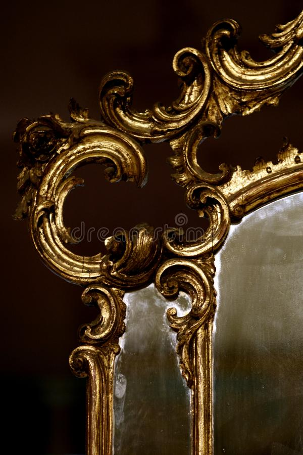 Antique gold mirror. Antique mirror with a gilded frame detail stock photo