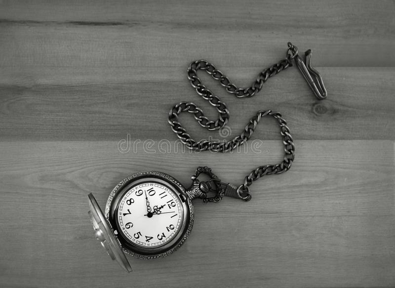 Antique gray metal pocket watch with chain displayed on a wood background. This photograph with an overhead perspective features an antique gray metal pocket stock image
