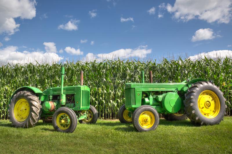 Antique Vintage Green John Deere Tractors in front of a corn field with a blue sky. royalty free stock photography