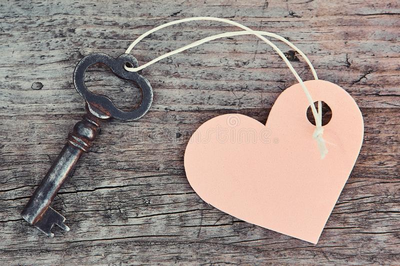 An antique handmade key with a heart-shaped label keychain lies on a wooden Board.  royalty free stock image